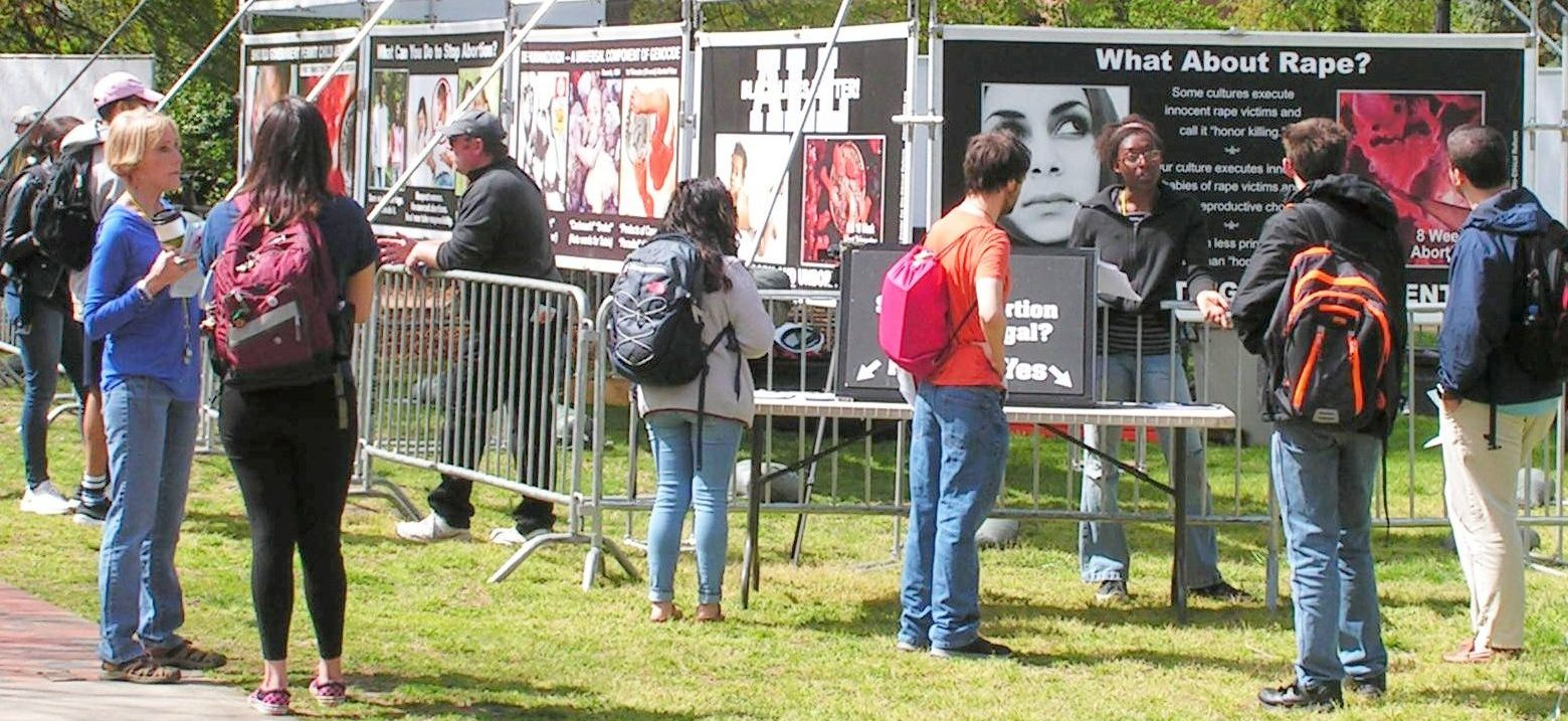 Center for Bio-Ethical Reform (CBR) Staff interact with Students at University North Carolina (UNC) Greensboro. Behind them are numerous vinyl banners comparing abortion to other forms of genocide.