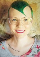"Head shot photo of director Abra Singleton, with shock of vivid florescent green hair and tattoo under collar bone reading, ""It's His breath in my lungs"""